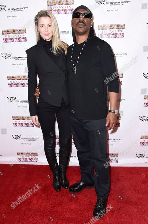 """Paige Butcher, left, and Eddie Murphy attend """"SUBCONSCIOUS"""" by Bria Murphy Gallery Opening at Lace Gallery, in Los Angeles"""