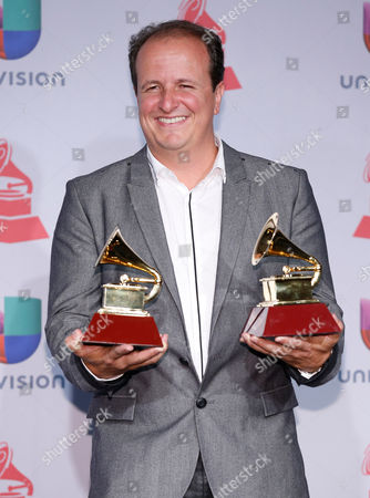 Julio Reyes Copello poses with the awards for best engineered album and record of the year backstage at the 14th Annual Latin Grammy Awards at the Mandalay Bay Hotel and Casino, in Las Vegas