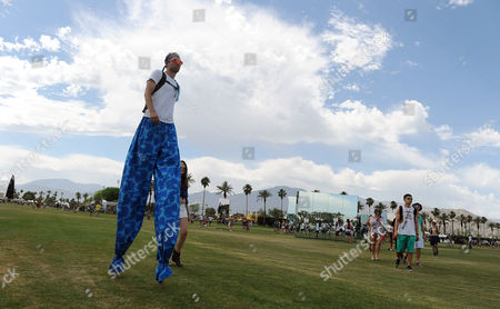 Matt White walks through the Empire Polo Field on stilts during day one of the 2014 Coachella Music and Arts Festival, in Indio, Calif