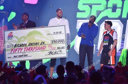 Stock Photo of Metta World Peace and from left, Tyson Chandler and Michael Strahan present a check for the $50,000 shot to Ricardo Jacobo, Jr. at the Kids' Choice Sports Awards at UCLA's Pauley Pavilion, in Los Angeles
