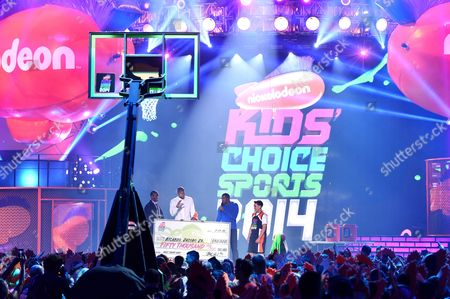 Stock Picture of Metta World Peace and from left, Tyson Chandler and Michael Strahan present a check for the $50,000 shot to Ricardo Jacobo, Jr. at the Kids' Choice Sports Awards at UCLA's Pauley Pavilion, in Los Angeles