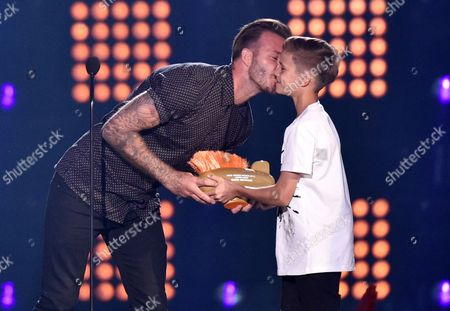 David Beckham, left, kisses his son Romeo James Beckham as he accepts the legend award at the Kids' Choice Sports Awards at UCLA's Pauley Pavilion, in Los Angeles