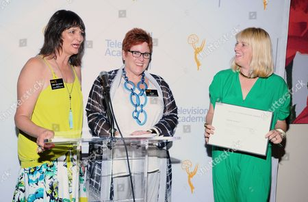 """The Television Academy's Terry Ann Gordon, from left, and Sue Bub present a plaque to Marie Schley for her Emmy nomination for """"Transparent"""" at The 9th Annual Outstanding Art of Television Costume Design Exhibition opening at the FIDM Museum & Galleries on the Park, in Los Angeles. The Television Academy and FIDM Museum honored this year's Emmy(R) Award winners in Outstanding Costume Design at the opening reception for this annual special exhibition"""