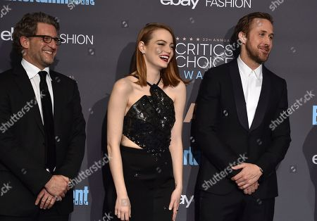 """Gary Gilbert, from left, Emma Stone, and Ryan Gosling, winners of the award for best picture for """"La La Land,"""" pose in the press room at the 22nd annual Critics' Choice Awards at the Barker Hangar, in Santa Monica, Calif"""