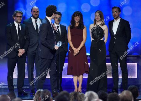 """Director Damien Chazelle, accepts the award for best picture for """"La La Land"""" at the 22nd annual Critics' Choice Awards at the Barker Hangar, in Santa Monica, Calif. Pictured on stage from left, Gary Gilbert, Jordan Horowitz, Justin Hurwitz, Mary Zophres, Emma Stone, and Ryan Gosling"""