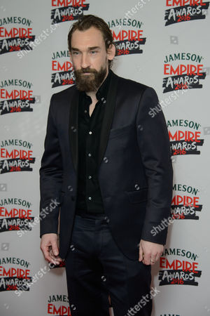 Joseph Mawle poses for photographers upon arrival at the 'Empire Film Awards' in London