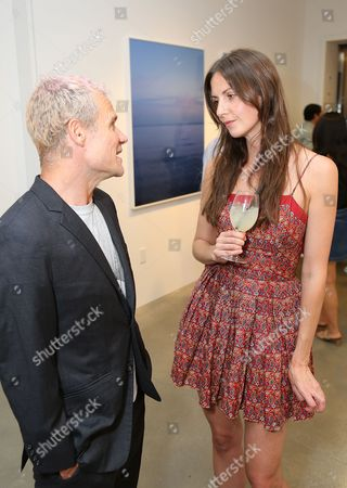 From left, Flea and Liz Carey talk during the reception for the inaugural exhibition at Regen Projects' new Hollywood gallery, in Los Angeles, Calif