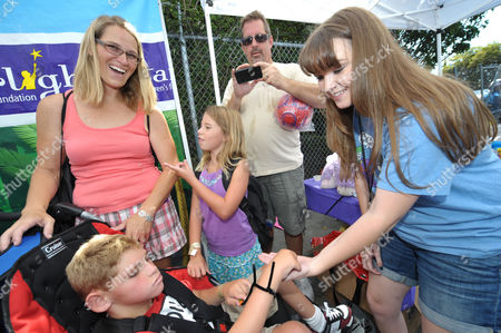COMMERCIAL IMAGE - Starlight StarPower Ambassador Kay Panabaker, right, greets children at the 2012 FAME Back-To-School event, in Los Angeles. The Starlight Children's Foundation invited families to participate in the event, where participants were given free school supplies and shoes