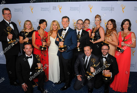 """Stock Image of Jim Roush, from back left, Laura Roush, Yun Lingner, Dominique Worden, Lori Greiner, Max Swedlow, Heather Drilling, Kate Ryu, Becky Blitz, Ian Sambor, from front left, Brandon Wallace, and Michael Kramer, winners of the award for outstanding structured reality program for """"Shark Tank"""", pose for a portrait at the Television Academy's Creative Arts Emmy Awards at Microsoft Theater, in Los Angeles"""