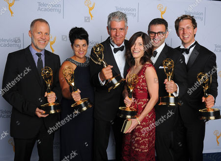 """Chris Collins, from left, Lydia Tenaglia, Anthony Bourdain, Sandra Zweig, Tom Vitale, Erik Osterholm, winners of the award for outstanding informational series or special for """"Anthony Bourdain: Parts Unknown"""", pose for a portrait at the Television Academy's Creative Arts Emmy Awards at Microsoft Theater, in Los Angeles"""