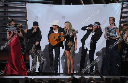 Hosts Carrie Underwood and Brad Paisley onstage with Korie and Jase Robertson (L) and Willie Robertson and Missy Robertson (R) of Duck Dynasty at The 47th Annual CMA Awards, on at Bridgestone Arena in Nashville, Tenn