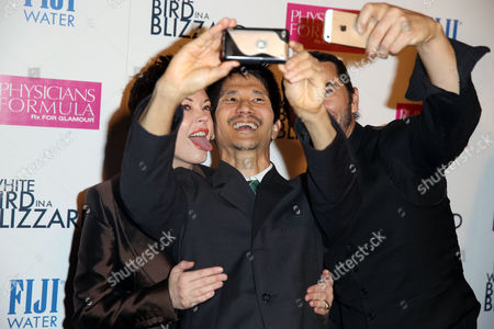 """Rose McGowan, left, writer and director Gregg Araki, center, and James Duval take a selfie at the premiere of """"White Bird in a Blizzard"""" presented by FIJI Water on in Los Angeles"""
