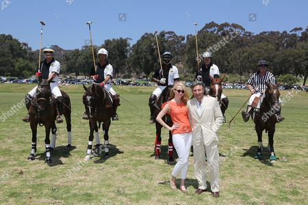From left, Actress Madison Walls and fashion designer Leon Max pose in front of the Max Studio Polo Team during the Will Rogers Dog Iron Polo Cup event at the Will Rogers State Historic Park polo field, in Pacific Palisades, Calif