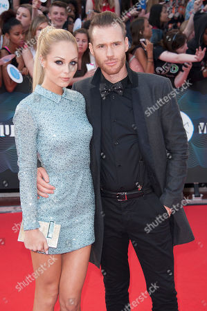 Laura Vandervoort and Oliver Trevena arrive on the red carpet during the 2014 MuchMusic Video Awads on in Toronto, Canada