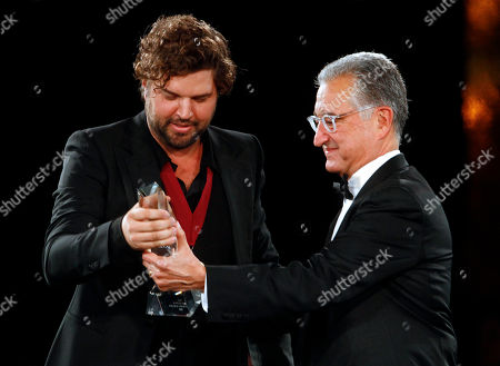 Dallas Davidson receives the Songwriter of the Year award from Del Bryant at the 60th Annual BMI Country Awards, in Nashville, Tenn