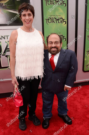 "Stock Picture of Amy Buchwald, left, and Danny Woodburn arrive at the Los Angeles premiere of ""Teenage Mutant Ninja Turtles"" at the Regency Village Theater on"