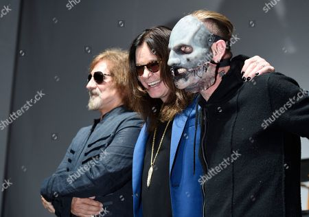 """Geezer Butler, from left, and Ozzy Osbourne of Black Sabbath pose with Corey Taylor of Slipknot during the """"Ozzfest Meets Knotfest"""" news conference at the Hollywood Palladium, in Los Angeles. The """"Ozzfest Meets Knotfest"""" multi-stage camping festival on Sept. 24-25 at the San Manuel Amphitheater and Festival Grounds in San Bernardino, Calif. was announced at the news conference"""