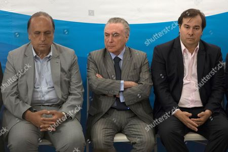 Michel Temer, Rodrigo Maia, Luiz Fernando Pezao. Brazil's president Michel Temer sits between the governor of Rio de Janeiro Luiz Fernando Pezao, left, and the president of the Chamber of Deputies Rodrigo Maia, right, as he attends a ceremony at the Brain Institute in Rio de Janeiro, Brazil, . Temer has been charged with obstruction of justice and of leading a criminal organization in the latest fallout from a wide-ranging corruption probe that has ensnared many of the elite in Latin America's largest nation