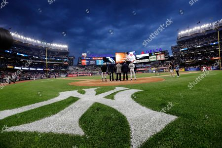 """Baltimore Orioles manager Buck Showalter, left, Paul O'Neill, second from left, Willie Randolph, David Cone and New York Yankees manager Joe Girardi pay their respects during a moment of silence for Gene """"Stick"""" Michael before a baseball game between the Yankees and the Orioles, in New York"""