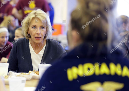 U.S. Secretary of Education Betsy DeVos talks with Gracie Johnson during a hog roast before a high school football game between Eastern Hancock and Knightstown, in Charlottesville, Ind