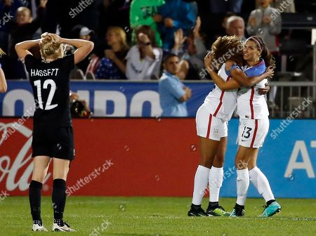 Betsy Hassett, Alex Morgan, Casey Short. New Zealand midfielder Betsy Hassett (12) reacts as U.S. forward Alex Morgan (13) is congratulated by Casey Short after scoring a goal during the second half of an international friendly soccer match in Commerce City, Colo