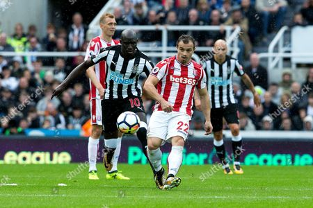 Stock Picture of Stoke City midfielder Xherdan Shaqiri (#22) passes the ball back to his goalkeeper under pressure from Newcastle United midfielder Mohamed Diam? (#10) during the Premier League match between Newcastle United and Stoke City at St. James's Park, Newcastle