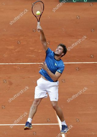 Croatia's Nikola Mektic plays a shot from Colombia's Juan Sebastian Cabal and Alejandro Falla, during their Davis Cup World Group play-offs doubles tennis match at the Santamaria Bullring in Bogota, Colombia