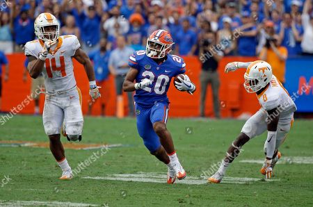 Florida running back Malik Davis (20) runs for yardage as he gets between Tennessee linebacker Quart'e Sapp (14) and defensive back Justin Martin (8) during the second half of an NCAA college football game, in Gainesville, Fla. Florida won 26-20