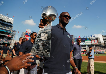 Former New York Giants player Plaxico Burress holds out the Super Bowl XLII Vince Lombardi trophy for fans to touch as he and teammates from the 2008 Super Bowl championship team walk around Yankee Stadium before a baseball game between the New York Yankees and the Baltimore Orioles, in New York