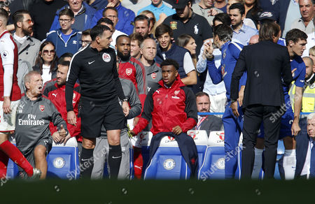 Chelsea coach Carlo Cudicini puts his finger to his lips as he argues with the Arsenal bench following an altercation after the Davod Luiz sending off