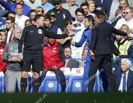4th Official Neil Swarbrick steps in to calm down Chelsea manager Antonio Conte and coach Carlo Cudicini after an altercation following the David Luiz sending off