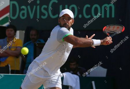 Stock Photo of Aisam-ul-Haq Qureshi, of Pakistan, returns the ball to Wishaya Trongcharoenchaikul, of Thailand, during the Davis Cup Asia Oceania Group II third round match at the Pakistan Sport Complex stadium in Islamabad, Pakistan