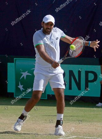 Aisam-ul-Haq Qureshi, of Pakistan, returns the ball to Wishaya Trongcharoenchaikul, of Thailand, during the Davis Cup Asia Oceania Group II third round match at the Pakistan Sport Complex in Islamabad, Pakistan
