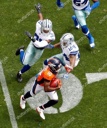 Denver Broncos wide receiver Emmanuel Sanders (10) eludes Dallas Cowboys cornerback Nolan Carroll (24) and free safety Byron Jones (31) during the first half of an NFL football game, in Denver