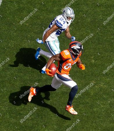 Denver Broncos wide receiver Demaryius Thomas (88) runs after the catch for a first down as Dallas Cowboys cornerback Nolan Carroll (24) pursues during the first half of an NFL football game, in Denver