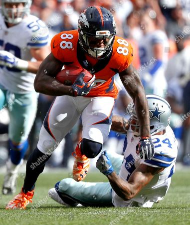 Denver Broncos wide receiver Demaryius Thomas (88) is hit by Dallas Cowboys cornerback Nolan Carroll (24) during the first half of an NFL football game, in Denver. Carroll was injured on the play and helped off the field