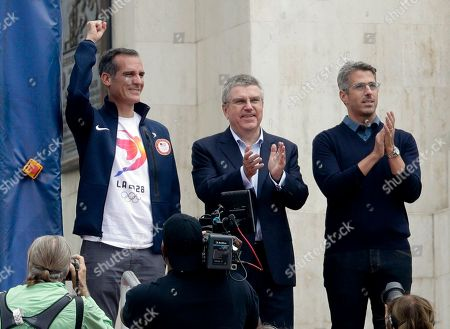 Stock Photo of Los Angeles Mayor Eric Garcetti, left, International Olympic Committee President Thomas Bach and LA 2028 Chairman Casey Wasserman greet fans before the first half of an NFL football game between the Los Angeles Rams and the Washington Redskins, in Los Angeles. The three were on hand to celebrate the announcement that the city will host the 2028 Olympic and Paralympic Games