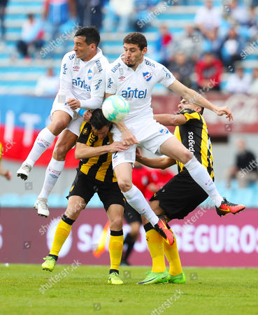 Penarol Maxi Rodriguez (2-L) vies for the ball with Nacional's Gonzalo Porras (L) and Agustin Rogel (2-R) during Clausura tournament soccer match between Penarol and Nacional in Montevideo, Uruguay, 17 September 2017.