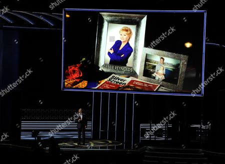 Stock Picture of Christopher Jackson, Debbie Reynolds. Christopher Jackson sings as a picture of Debbie Reynolds appears onscreen during an in memoriam tribute at the 69th Primetime Emmy Awards, at the Microsoft Theater in Los Angeles