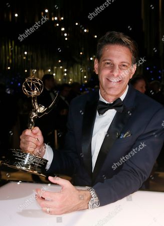 """Lee Metzger poses with his award for for outstanding reality-competition program for """"The Voice"""" at the Governors Ball for the 69th Primetime Emmy Awards at the Los Angeles Convention Center, in Los Angeles"""