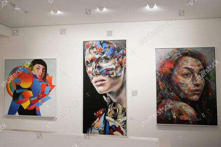 "The paintings, from left, 'Dropper"" by Eric Jones, 'La Cage Entre Victoire Et Defaite' by Sandra Chevrier and 'The Distance Between Is Equal' by David Walker are displayed inside the exhibition of the new Urban Nation Museum for Urban Contemporary Art in Berlin, Germany, . The opening exhibition, which will last for around nine months, aims to introduce visitors to the culture of urban art. Director Yasha Young worked with eight curators from various countries to produce a show that explores strands including portraits, pop art and activism"