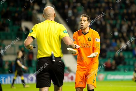 Livingston goalkeeper Neil Alexander (#1) protests the award of a penalty kick to Hibernian with referee Bobby Madden during the Betfred Scottish Cup match between Hibernian and Livingston at Easter Road, Edinburgh