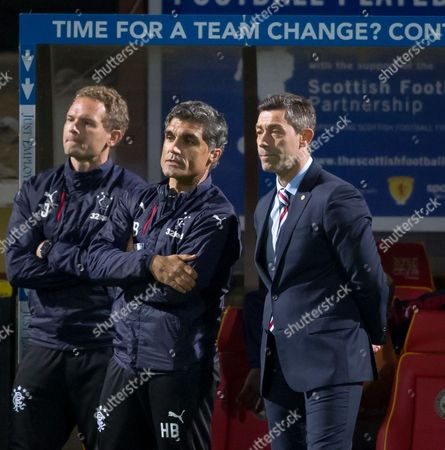 """Rangers First Team Coach Jonatan Johansson, Rangers assistant manager Helder Batista & Rangers Manager Pedro Caixinha (right) under a sign reading """"time for a team change?"""" in the technical area"""
