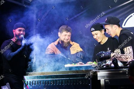Stock Image of Ramzan Kadyrov, Timur Yunusov. On, Chechnya's regional leader Ramzan Kadyrov, center, and Russian rapper Timur Yunusov attend a show in a Black Star Burger restaurant in Grozny, Russia . Yunusov, known under the stage name Timati, was in Chechnya's capital Grozny to open the city's first restaurant of his Black Star Burger chain