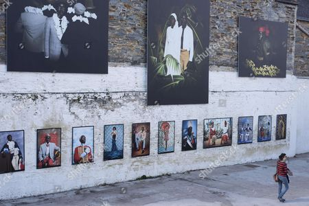 Stock Image of A woman walks past pictures by photographer Omar Victor Diop
