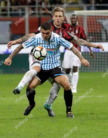 Spal's Federico Viviani, foreground, is challenged by AC Milan's Lucas Biglia during the Serie A soccer match between AC Milan and Spal, at the Milan San Siro Stadium, Italy