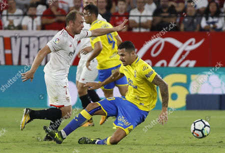 Sevilla FC's Danish midfielder Michael Krohn-Dehli (L) escapes from Victor Machin 'Vitolo' of UD Las Palmas during their Spanish Primera Division soccer match played at the Ramon Sanchez-Pizjuan in Sevilla, southern Spain, 20 September 2017.