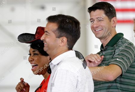 Speaker of the House Paul Ryan, of Wis., right, smiles with Rep. Carlos Curbelo, R-Fla., center, and Rep. Frederica Wilson, D-Fla., left, before a news briefing at the Coast Guard Air Station Miami, in Opa-locka, Fla. Ryan toured the Florida Keys to assess the damage caused by Hurricane Irma