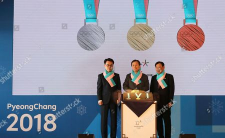 Stock Photo of Do Jong-hwan, Lee Hee-beom, Song Suk-doo. South Korean Culture, Sports and Tourism Minister Do Jong-hwan, center, Pyeongchang Organizing Committee for the 2018 Olympic and Paralympic Winter Games Lee Hee-beom, right, and Gangwon Province Vice Gov. Song Suk-doo stand with the silver, gold and bronze medals for the Pyeongchang 2018 Winter Olympics during an unveiling ceremony in Seoul, South Korea, . South Korea's Pyeongchang is the host city of the winter games which will be held from February 2018