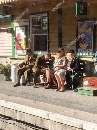 """Picture shows extras on Harman's Cross station in Dorset on Sept 19th,the set for a new  James Norton film set in Second World War. Actor James Norton has been spotted dressed as a SOLDIER as he filmed a new low-budget Second World War movie yesterday (Tues). The 32-year-old was seen donning an army uniform as he sat on a train in Swanage, where he is shooting the film which co-stars Downton Abbey actress Jessica Brown Findlay. The Happy Valley star was spotted chatting on his mobile phone as he made the journey from Swanage to Harman's Cross, where he joined an extensive crew of extras. Ben Parker, who was travelling with his mum on the train, said: """"It was very strange to get on the train and see James Norton sat there in costume."""